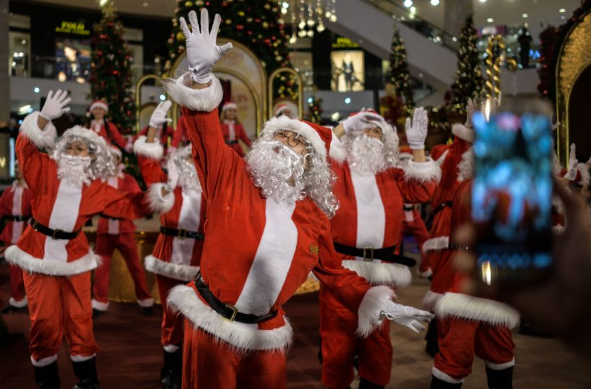 Performers clad in Santa Claus outfits dance at a shopping mall in Kuala Lumpur on December 18, 2017. Every year as Christmas approaches, shopping malls across Malaysia are decorated with beautiful light displays and offer year-end discounts to lure shoppers. / AFP PHOTO / MOHD RASFAN (Photo credit should read MOHD RASFAN/AFP/Getty Images)