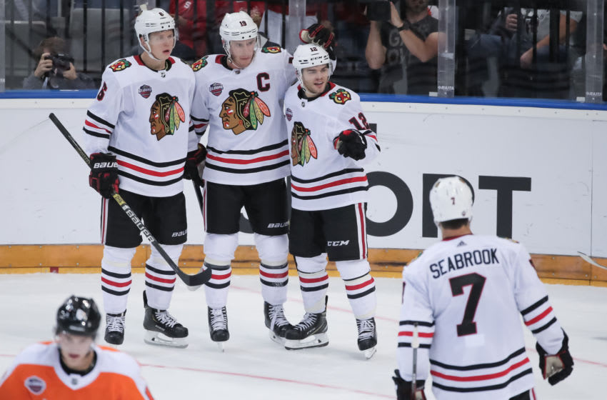 PRAGUE, CZECH REPUBLIC - OCTOBER 4: Alex DeBrincat #12 of the Chicago Blackhawks celebrates his second period goal against the Philadelphia Flyers with teammates Olli Maatta #6, Jonathan Toews #19 and Brent Seabrook #7 during the Global Series Challenge game at O2 Arena on October 4, 2019 in Prague, Czech Republic. (Photo by Andre Ringuette/NHLI via Getty Images)