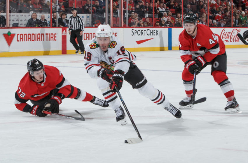 OTTAWA, ON - JANUARY 14: Jonathan Toews #19 of the Chicago Blackhawks stickhandles the puck in overtime against Thomas Chabot #72 and Jean-Gabriel Pageau #44 of the Ottawa Senators at Canadian Tire Centre on January 14, 2020 in Ottawa, Ontario, Canada. (Photo by Andre Ringuette/NHLI via Getty Images)