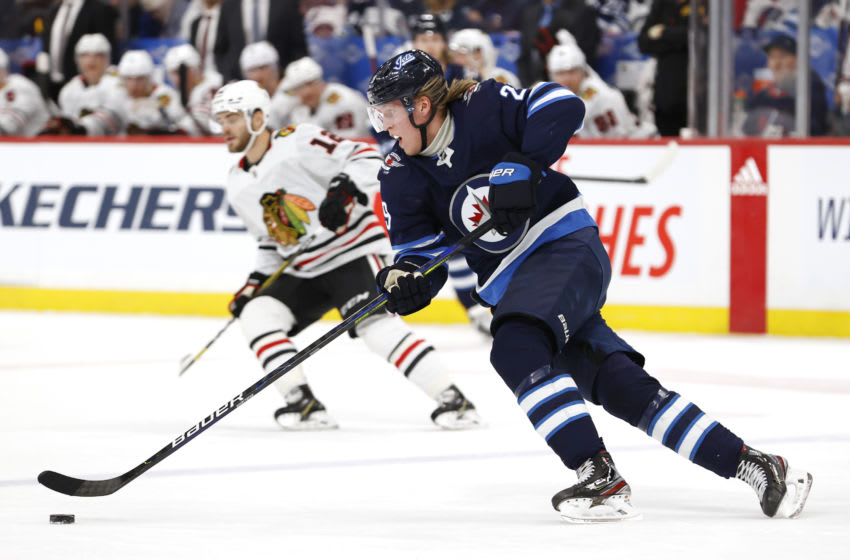Feb 16, 2020; Winnipeg, Manitoba, CAN; Winnipeg Jets right wing Patrik Laine (29) skates up the ice past Chicago Blackhawks left wing Alex DeBrincat (12) in the first period at Bell MTS Place. Mandatory Credit: James Carey Lauder-USA TODAY Sports