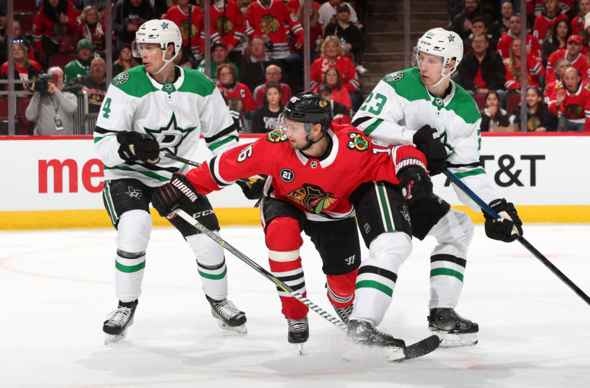 CHICAGO, IL - FEBRUARY 24: Marcus Kruger #16 of the Chicago Blackhawks watches for the puck in between Miro Heiskanen #4 and Esa Lindell #23 of the Dallas Stars in the second period at the United Center on February 24, 2019 in Chicago, Illinois. (Photo by Chase Agnello-Dean/NHLI via Getty Images)