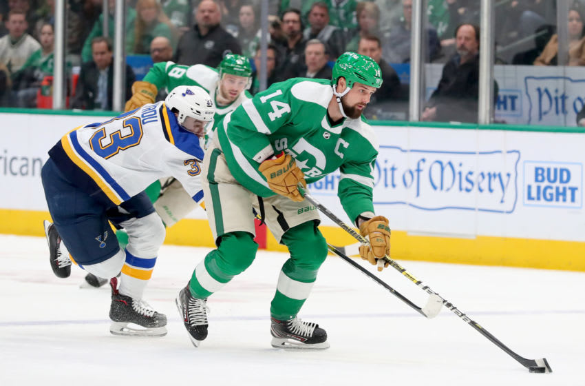 DALLAS, TEXAS - FEBRUARY 21: Jamie Benn #14 of the Dallas Stars controls the puck against Jordan Kyrou #33 of the St. Louis Blues in the second period at American Airlines Center on February 21, 2020 in Dallas, Texas. (Photo by Tom Pennington/Getty Images)