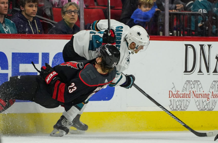 RALEIGH, NC - OCTOBER 26: Carolina Hurricanes Left Wing Brock McGinn (23) goes feet first into the boards behind San Jose Sharks Center Dylan Gambrell (14) during a game between the Carolina Hurricanes and the San Jose Sharks at the PNC Arena in Raleigh, NC on October 26, 2018. Carolina defeated San Jose 4-3 in a shootout. (Photo by Greg Thompson/Icon Sportswire via Getty Images)
