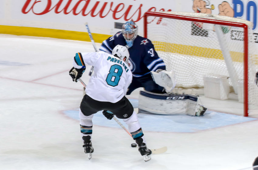WINNIPEG, MB - MARCH 12: Joe Pavelski #8 of the San Jose Sharks carries the puck towards the goal as goaltender Connor Hellebuyck #37 defends the net during third period action at the Bell MTS Place on March 12, 2019 in Winnipeg, Manitoba, Canada. (Photo by Jonathan Kozub/NHLI via Getty Images)