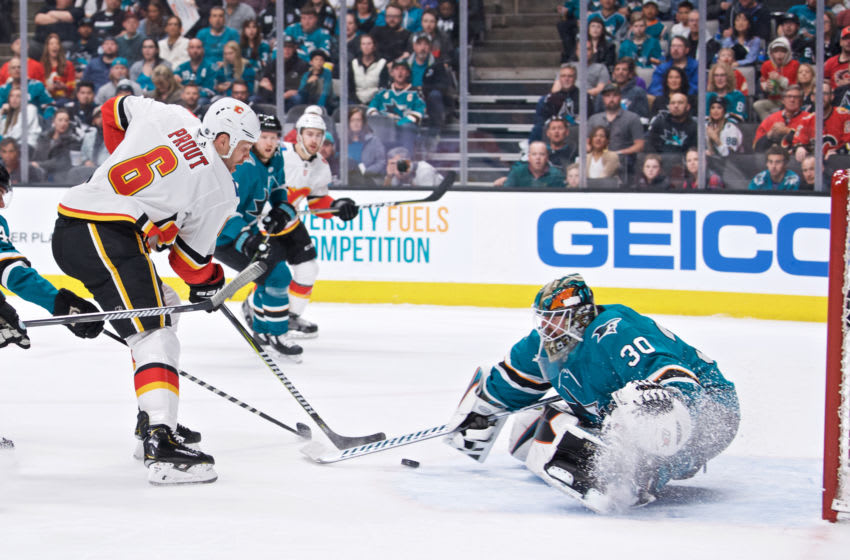 SAN JOSE, CA - MARCH 31: Calgary Flames defenseman Dalton Prout (6) carries the puck at San Jose Sharks goaltender Aaron Dell (30) during the San Jose Sharks game versus the Calgary Flames on March 31, 2019, at SAP Center at San Jose in San Jose, CA.