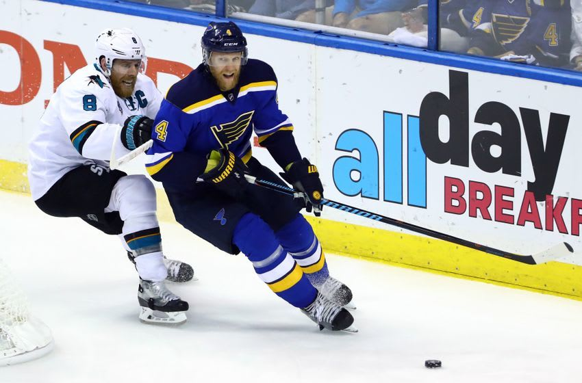 May 23, 2016; St. Louis, MO, USA; St. Louis Blues defenseman Carl Gunnarsson (4) and San Jose Sharks center Joe Pavelski (8) race for a loose puck during the third period in game five of the Western Conference Final of the 2016 Stanley Cup Playoffs at Scottrade Center. The Sharks won the game 6-3. Mandatory Credit: Billy Hurst-USA TODAY Sports