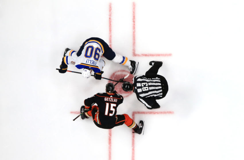 ANAHEIM, CALIFORNIA - MARCH 11: Ryan Getzlaf #15 of the Anaheim Ducks faces off with Ryan O'Reilly #90 of the St. Louis Blues as linesman Matt MacPherson #83 drops the puck during the second period of a game at Honda Center on March 11, 2020 in Anaheim, California. (Photo by Sean M. Haffey/Getty Images)