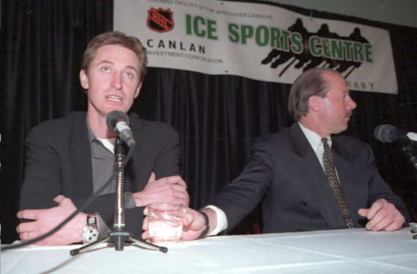 VANCOUVER, CANADA: St. Louis Blue's coach Mike Keenan (R) hands newest team player Wayne Gretzky (L) a glass of water 28 February during a press conference in Vancouver, Canada, after being traded from the Los Angeles Kings. Gretzky will play his first game with the blues against the Canucks 29 February. AFP PHOTO Dan LEVINE (Photo credit should read DAN LEVINE/AFP via Getty Images)