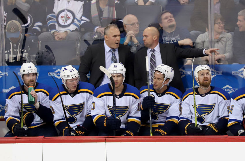 WINNIPEG, MB - FEBRUARY 9: Associate Coach Craig Berube and Head Coach Mike Yeo of the St. Louis Blues discuss strategy on the bench during second period action against the Winnipeg Jets at the Bell MTS Place on February 9, 2018 in Winnipeg, Manitoba, Canada. (Photo by Darcy Finley/NHLI via Getty Images)