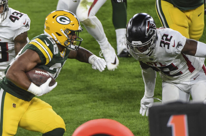 Oct 5, 2020; Green Bay, Wisconsin, USA; Green Bay Packers running back AJ Dillon (28) tries to evade a tackle by Atlanta Falcons safety Jaylinn Hawkins (32) in the second quarter at Lambeau Field. Mandatory Credit: Benny Sieu-USA TODAY Sports