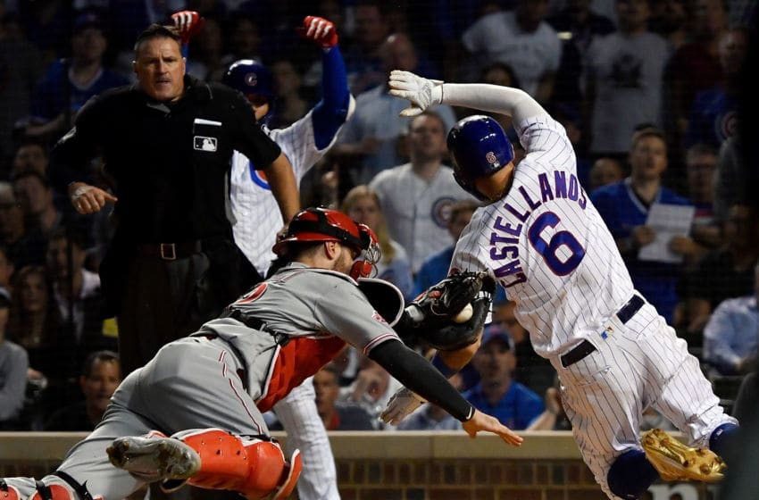 CHICAGO, ILLINOIS - SEPTEMBER 18: Nicholas Castellanos #6 of the Chicago Cubs beats the tag from Curt Casali #12 of the Cincinnati Reds to score in the fourth inning at Wrigley Field on September 18, 2019 in Chicago, Illinois. (Photo by Quinn Harris/Getty Images)