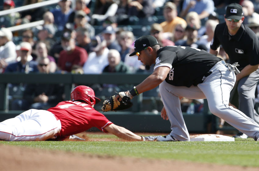 GOODYEAR, ARIZONA - FEBRUARY 23: Shogo Akiyama #4 of the Cincinnati Reds dives back to first base as Jose Abreu #76 of the Chicago White Sox attempts to apply the tag. (Photo by Ralph Freso/Getty Images)