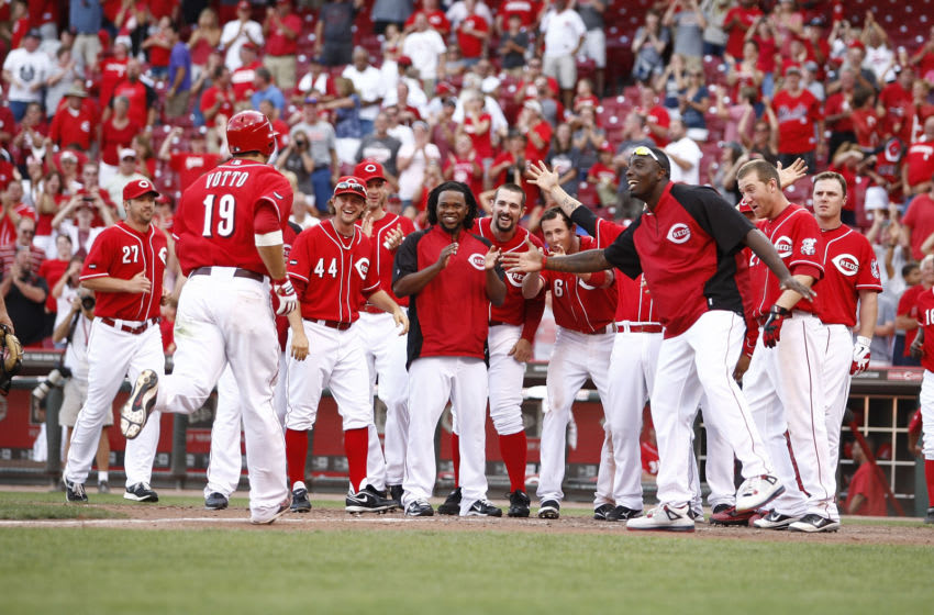 CINCINNATI, OH - AUGUST 28: Joey Votto #19 of the Cincinnati Reds is greeted by teammates after hitting a game-winning solo home run during the game against the Washington Nationals on August 28, 2011 at Great American Ball Park in Cincinnati, Ohio. The Reds defeated the Nationals 5-4 in 14 innings. (Photo by John Grieshop/Getty Images)