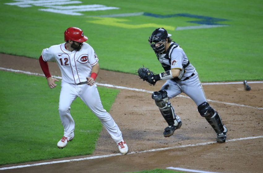 CINCINNATI, OHIO - SEPTEMBER 16: Curt Casalli #12 of the Cincinnati Reds is chased in a rundown by John Ryan Murphy #18 of the Pittsburgh Pirates. The Reds are currently in the MLB Playoffs. (Photo by Andy Lyons/Getty Images)