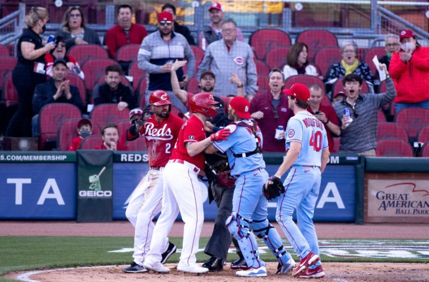 St. Louis Cardinals starting pitcher Jake Woodford (40) and St. Louis Cardinals catcher Yadier Molina (4) charge Cincinnati Reds right fielder Nick Castellanos (2) as Cincinnati Reds second baseman Jonathan India (6) holds them back in the fourth inning.