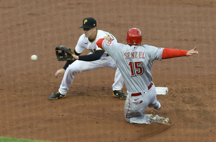 May 11, 2021; Pittsburgh, Pennsylvania, USA; Pittsburgh Pirates shortstop Kevin Newman (L) takes a throw before tagging out Cincinnati Reds second baseman Nick Senzel (15) attempting to steal second base. Mandatory Credit: Charles LeClaire-USA TODAY Sports