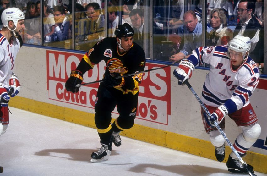 Geoff Courtnall #14 of the Vancouver Canucks defends against Alex Kovalev #27 and Sergei Zubov #21 of the New York Rangers during Game 5 of the 1994 Stanley Cup Finals . (Photo by B Bennett/Getty Images)