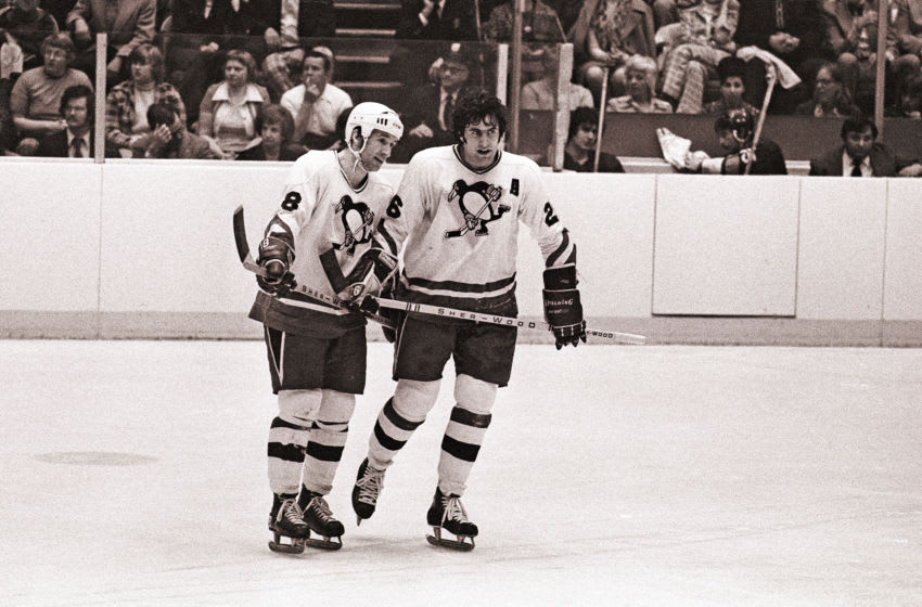 PITTSBURGH, PA - CIRCA 1976: (EDITORS NOTE: Image has been shot in black and white. Color version not available.) Winger Lowell MacDonald #18 and center Syl Apps, Jr. #26 of the Pittsburgh Penguins look on from the ice during a timeout during a National Hockey League game at the Civic Arena circa 1976 in Pittsburgh, Pennsylvania. (Photo by George Gojkovich/Getty Images)
