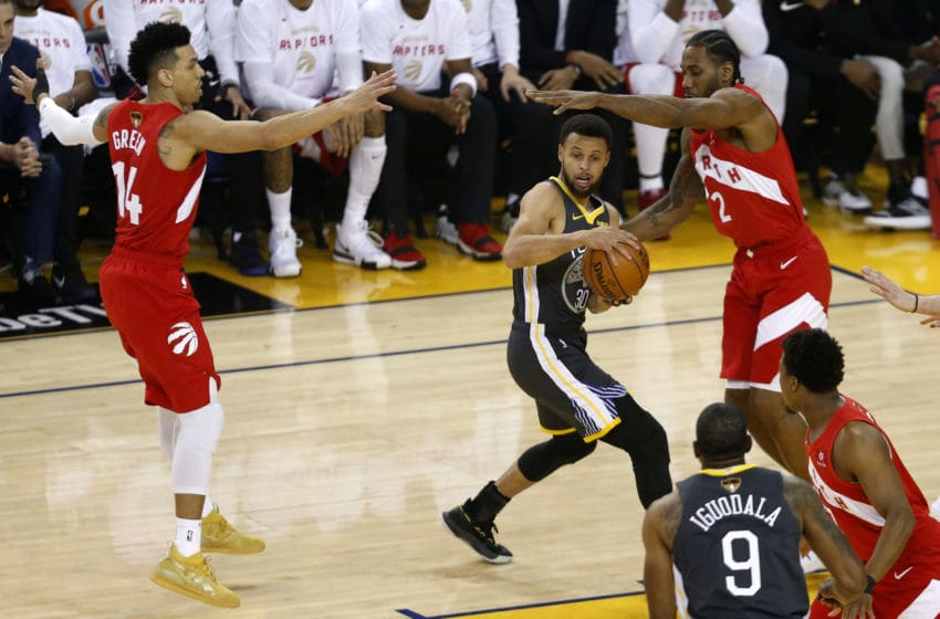 OAKLAND, CALIFORNIA - JUNE 07: Stephen Curry #30 of the Golden State Warriors is defended by Danny Green #14 and Kawhi Leonard #2 of the Toronto Raptors in the first half during Game Four of the 2019 NBA Finals at ORACLE Arena on June 07, 2019 in Oakland, California. NOTE TO USER: User expressly acknowledges and agrees that, by downloading and or using this photograph, User is consenting to the terms and conditions of the Getty Images License Agreement. (Photo by Lachlan Cunningham/Getty Images)