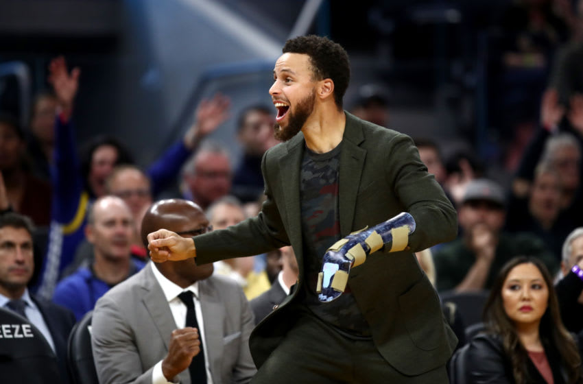 SAN FRANCISCO, CALIFORNIA - NOVEMBER 25: Injured Stephen Curry #30 of the Golden State Warriors reacts on the bench after the Warriors made a basket against the Oklahoma City Thunder at Chase Center on November 25, 2019 in San Francisco, California. NOTE TO USER: User expressly acknowledges and agrees that, by downloading and or using this photograph, User is consenting to the terms and conditions of the Getty Images License Agreement. (Photo by Ezra Shaw/Getty Images)