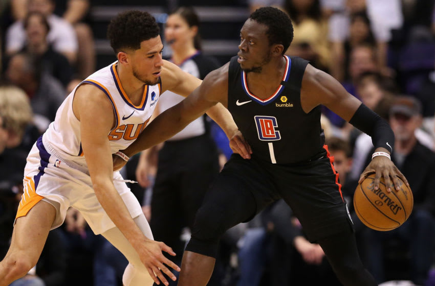 PHOENIX, ARIZONA - FEBRUARY 26: Reggie Jackson #1 of the LA Clippers handles the ball against Devin Booker #1 of the Phoenix Suns during the second half of the NBA game at Talking Stick Resort Arena on February 26, 2020 in Phoenix, Arizona. The Clippers defeated the Suns 102-92. NOTE TO USER: User expressly acknowledges and agrees that, by downloading and or using this photograph, user is consenting to the terms and conditions of the Getty Images License Agreement. Mandatory Copyright Notice: Copyright 2020 NBAE. (Photo by Christian Petersen/Getty Images)