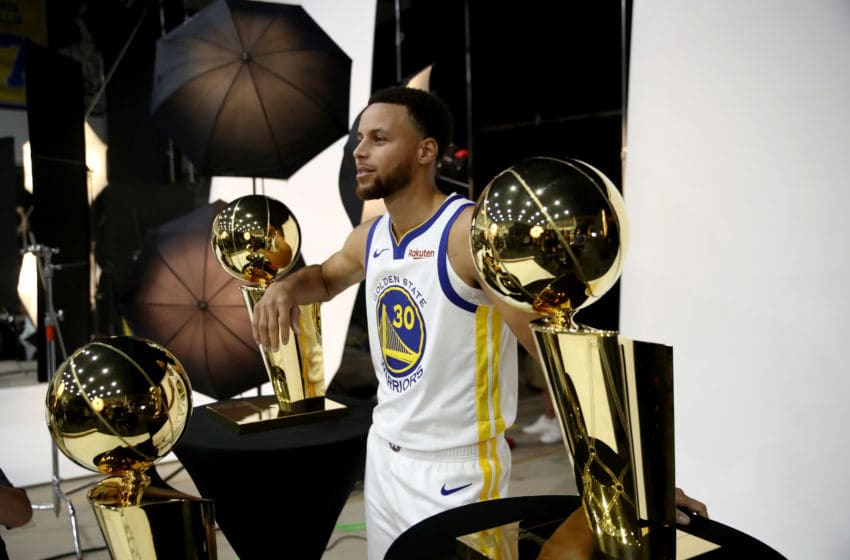 OAKLAND, CA - SEPTEMBER 24: Stephen Curry #30 of the Golden State Warriors poses with three Larry O'Brien NBA Championship Trophies during the Golden State Warriors media day on September 24, 2018 in Oakland, California. (Photo by Ezra Shaw/Getty Images)