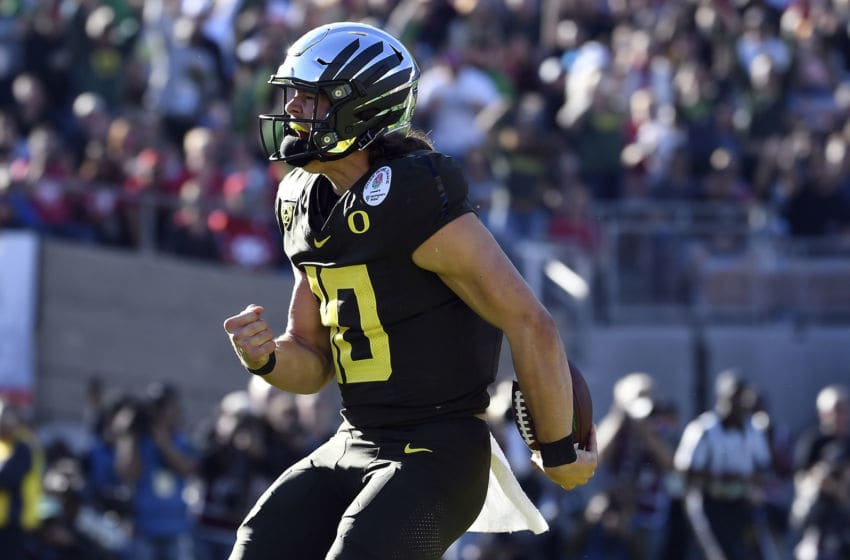 PASADENA, CALIFORNIA - JANUARY 01: Justin Herbert #10 of the Oregon Ducks celebrates after scoring a four yard touchdown against the Wisconsin Badgers during the first quarter in the Rose Bowl game presented by Northwestern Mutual at Rose Bowl on January 01, 2020 in Pasadena, California. (Photo by Kevork Djansezian/Getty Images)