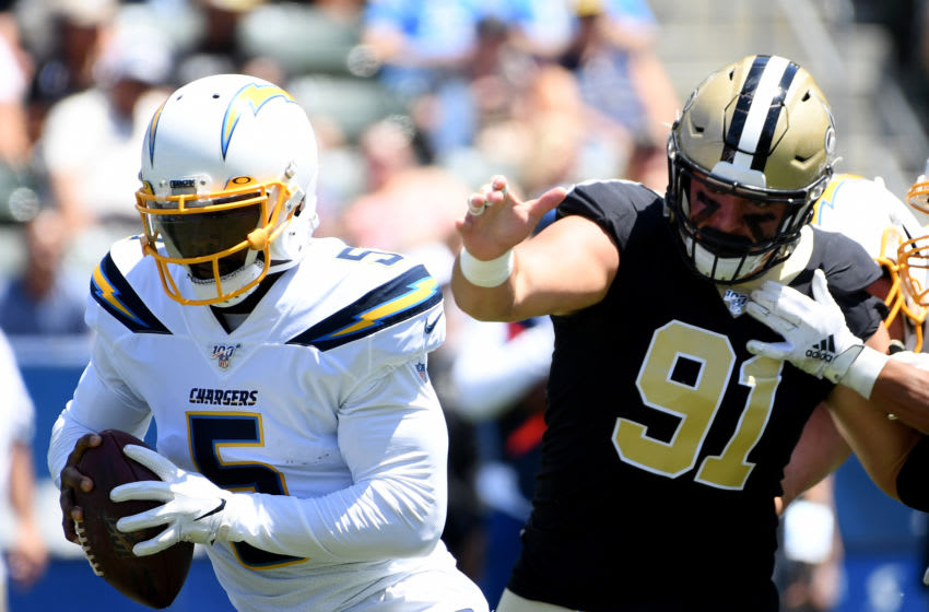 CARSON, CALIFORNIA - AUGUST 18: Tyrod Taylor #5 of the Los Angeles Chargers avoids the rush from Trey Hendrickson #91 of the New Orleans Saints in a 19-17 Saints win during a preseason game at Dignity Health Sports Park on August 18, 2019 in Carson, California. (Photo by Harry How/Getty Images)