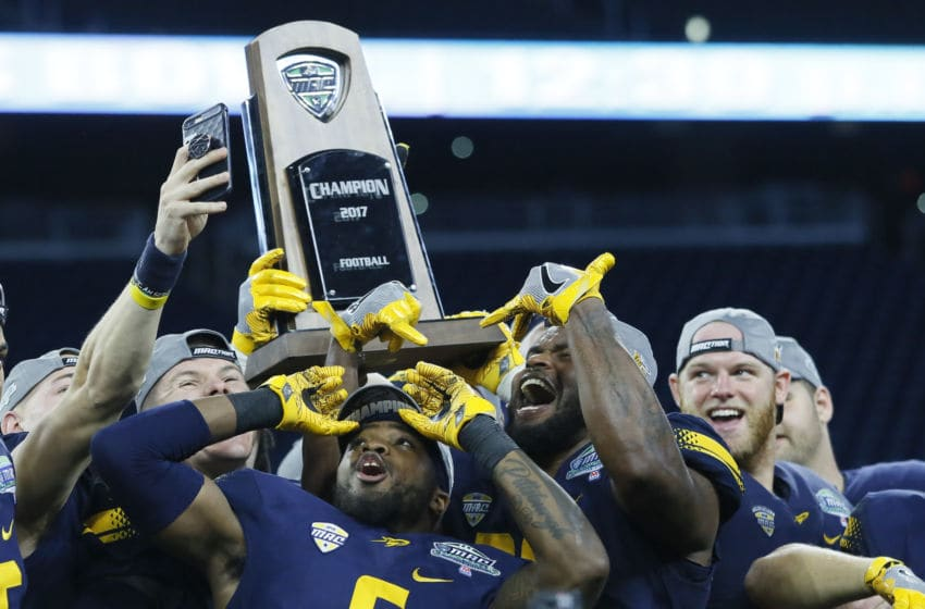 DETROIT, MI - DECEMBER 02: Cornerback Trevon Mathis #6 of the Toledo Rockets and linebacker Ja'Wuan Woodley #30 of the Toledo Rockets celebrate with teammates and the MAC Championship trophy following a 45-28 win over the Akron Zips at Ford Field on December 2, 2017 in Detroit, Michigan. (Photo by Duane Burleson/Getty Images)
