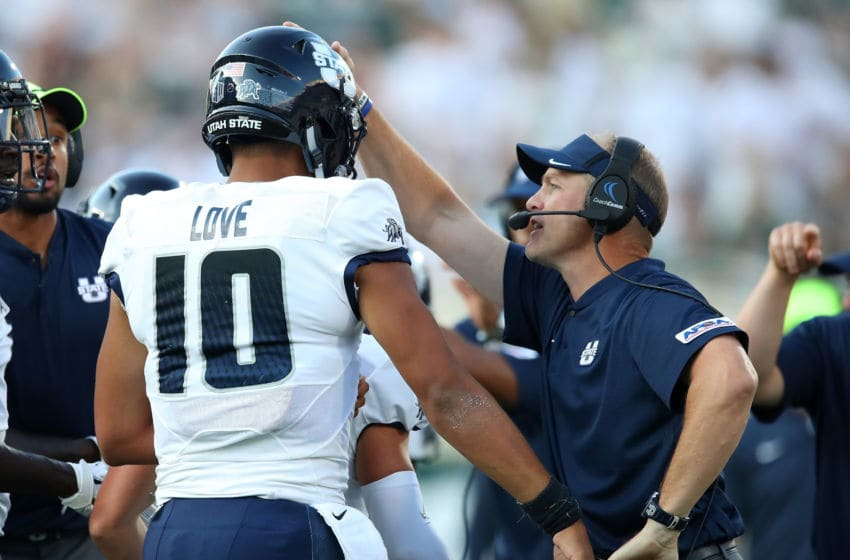 EAST LANSING, MI - AUGUST 31: Head coach Matt Wells of the Utah State Aggies celebrates with Jordan Love #10 after he scored a first half touchdown against the Michigan State Spartans at Spartan Stadium on August 31, 2018 in East Lansing, Michigan. (Photo by Gregory Shamus/Getty Images)