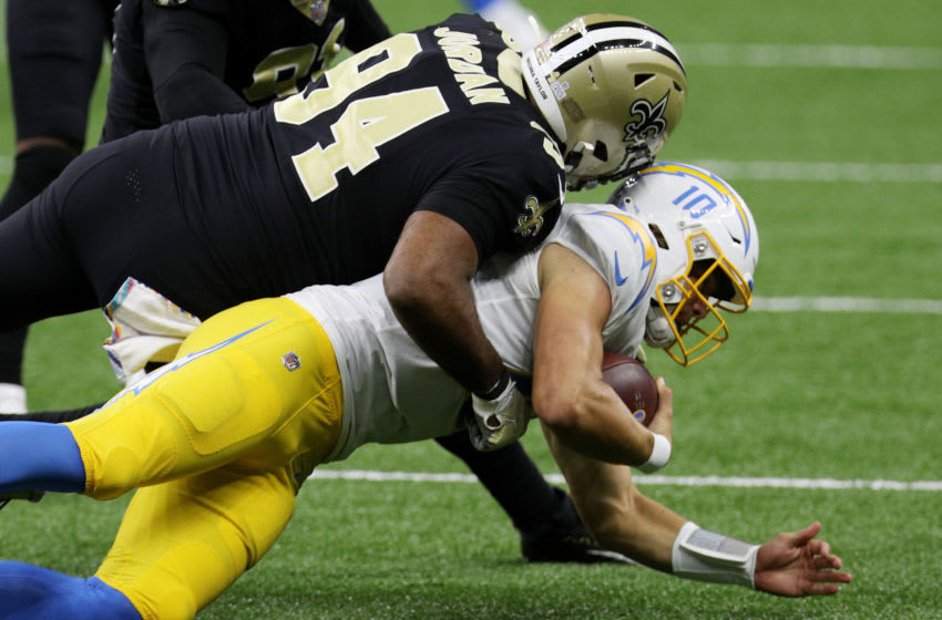 NEW ORLEANS, LOUISIANA - OCTOBER 12: Justin Herbert #10 of the Los Angeles Chargers is tackled by Cameron Jordan #94 of the New Orleans Saints during their NFL game at Mercedes-Benz Superdome on October 12, 2020 in New Orleans, Louisiana. (Photo by Chris Graythen/Getty Images)