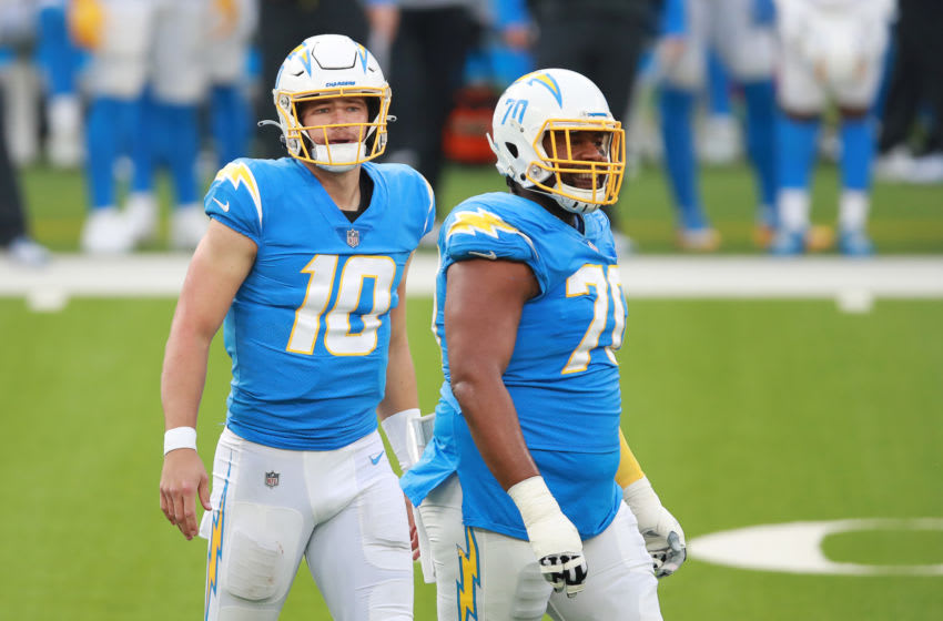 INGLEWOOD, CALIFORNIA - DECEMBER 27: Justin Herbert #10 of the Los Angeles Chargers and Trai Turner #70 react in the middle of the field in the second quarter against the Denver Broncos at SoFi Stadium on December 27, 2020 in Inglewood, California. (Photo by Joe Scarnici/Getty Images)