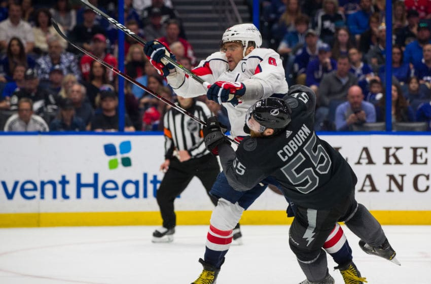 TAMPA, FL - MARCH 30: Braydon Coburn #55 of the Tampa Bay Lightning is checked by Alex Ovechkin #8 of the Washington Capitals at Amalie Arena on March 30, 2019 in Tampa, Florida. (Photo by Mark LoMoglio/NHLI via Getty Images)