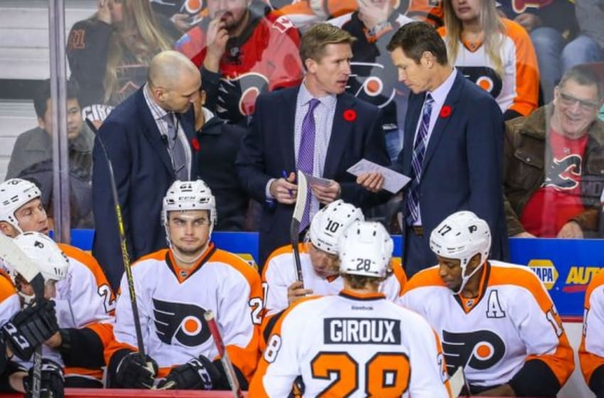 Nov 5, 2015; Calgary, Alberta, CAN; Philadelphia Flyers head coach Dave Hakstol (middle) on his bench against the Calgary Flames during the overtime period at Scotiabank Saddledome. Calgary Flames won 2-1. Mandatory Credit: Sergei Belski-USA TODAY Sports
