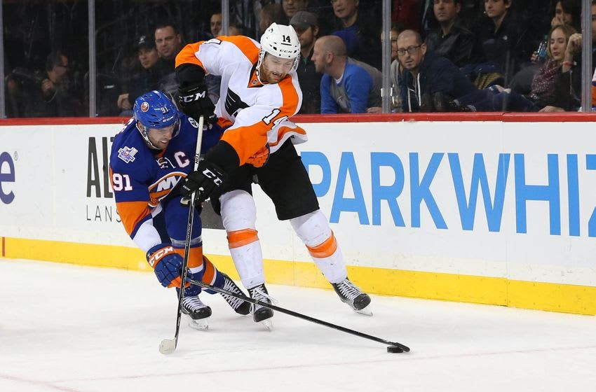 Nov 25, 2015; Brooklyn, NY, USA; New York Islanders center John Tavares (91) keeps the puck as Philadelphia Flyers center Sean Couturier (14) leans in during the third period at Barclays Center. New York Islanders won 3-1. Mandatory Credit: Anthony Gruppuso-USA TODAY Sports