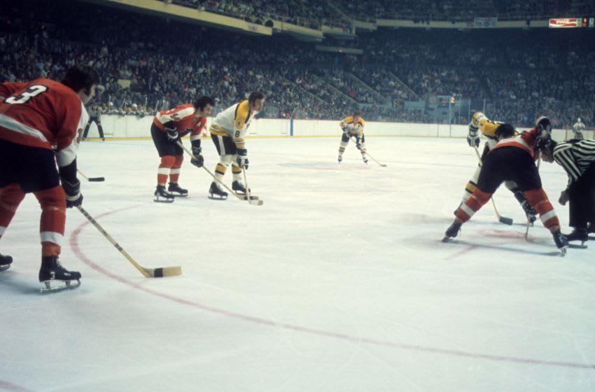 Ken Hodge, Boston Bruins, Joe Watson and Tom Bladon, Philadelphia Flyers (Photo by Melchior DiGiacomo/Getty Images)