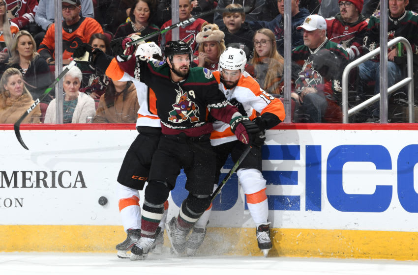 GLENDALE, ARIZONA - JANUARY 04: Brad Richardson #15 of the Arizona Coyotes battles for the puck along the boards with Nicolas Aube-Kubel #62 and Matt Niskanen #15 of the Philadelphia Flyers during the second period of the NHL hockey game at Gila River Arena on January 04, 2020 in Glendale, Arizona. (Photo by Norm Hall/NHLI via Getty Images)