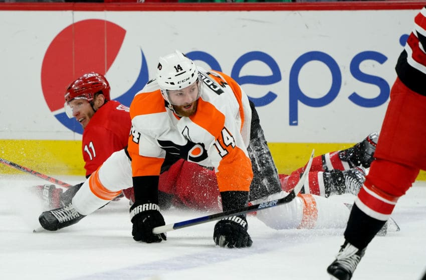 RALEIGH, NC - JANUARY 7: Jordan Staal #11 of the Carolina Hurricanes and Sean Couturier #14 of the Philadelphia Flyers collide during an NHL game on January 7, 2020 at PNC Arena in Raleigh, North Carolina. (Photo by Gregg Forwerck/NHLI via Getty Images)