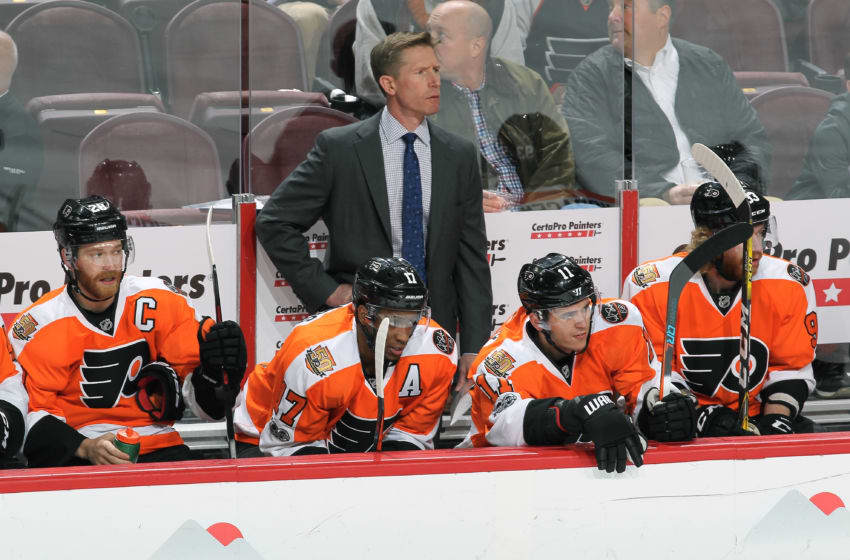 PHILADELPHIA, PA - MARCH 13: Head Coach Dave Hakstol of the Philadelphia Flyers follows the play on the ice behind Claude Giroux