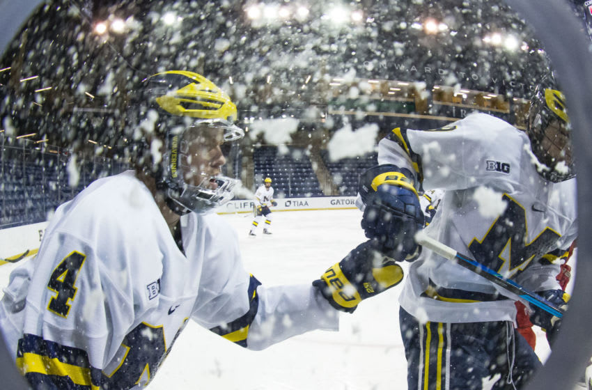 Mar 14, 2021; South Bend, IN, USA; Ice falls from the air as Michigan's Cam York (4) and Brendan Brisson (19) come to a stop during the Michigan vs. Ohio State Big Ten Hockey Tournament game Sunday, March 14, 2021 at the Compton Family Ice Arena in South Bend. Mandatory Credit: Michael Caterina-USA TODAY Sports