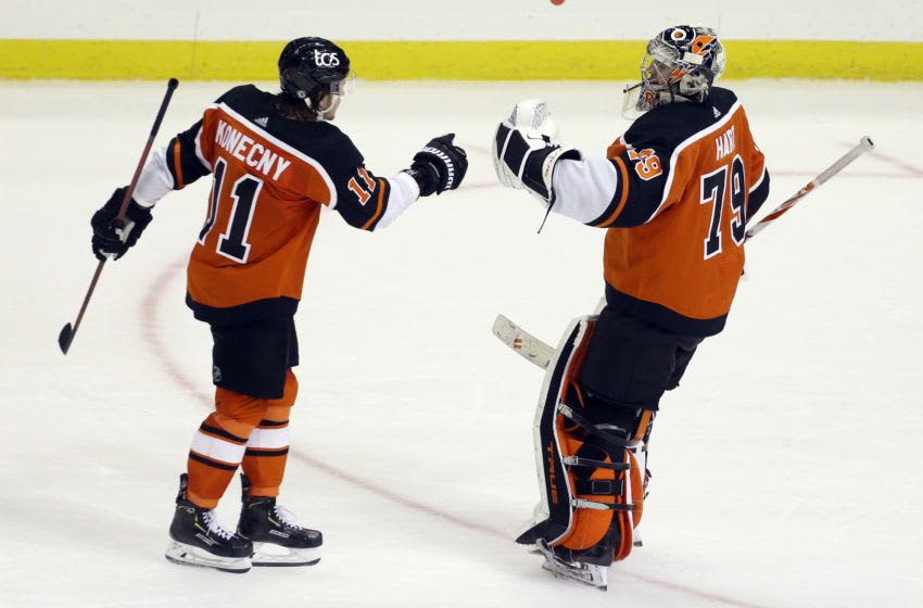 Apr 15, 2021; Pittsburgh, Pennsylvania, USA; Philadelphia Flyers right wing Travis Konecny (11) and goaltender Carter Hart (79) celebrate after defeating the Pittsburgh Penguins in a shootout at PPG Paints Arena. The Flyers won 2-1 in a shootout. Mandatory Credit: Charles LeClaire-USA TODAY Sports