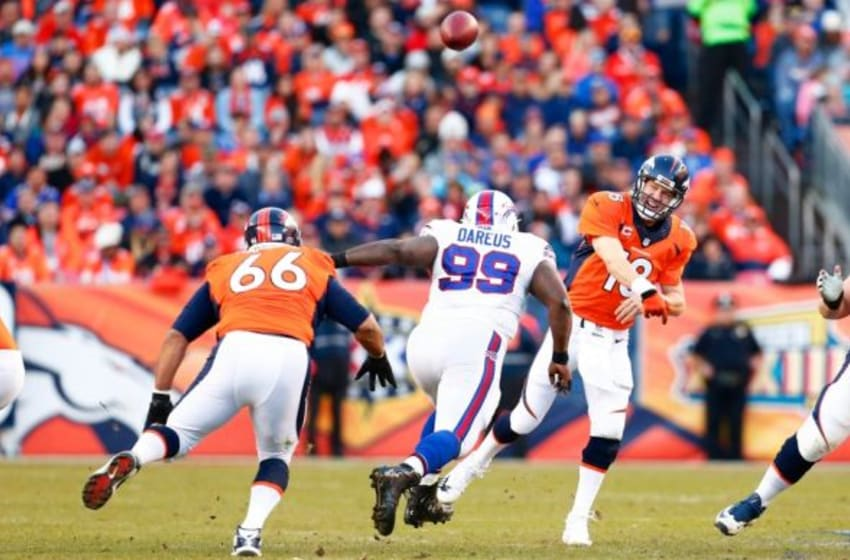 Dec 7, 2014; Denver, CO, USA; Denver Broncos quarterback Peyton Manning (18) throws the ball over center Manny Ramirez (66) under pressure from Buffalo Bills defensive tackle Marcell Dareus (99). The Broncos defeated the Bills 24-17. Mandatory Credit: Isaiah J. Downing-USA TODAY Sports