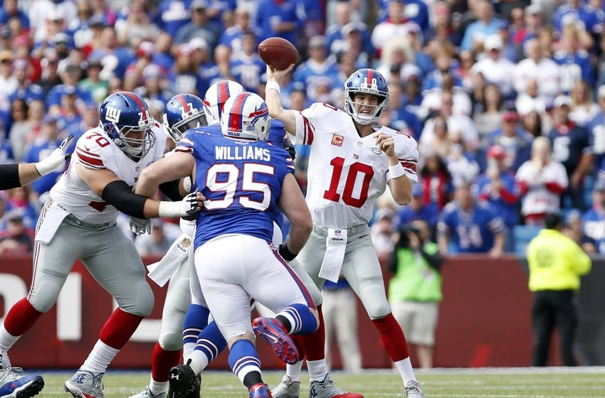 Oct 4, 2015; Orchard Park, NY, USA; New York Giants quarterback Eli Manning (10) throws a pass under pressure by Buffalo Bills defensive tackle Kyle Williams (95) during the first quarter at Ralph Wilson Stadium. Mandatory Credit: Kevin Hoffman-USA TODAY Sports