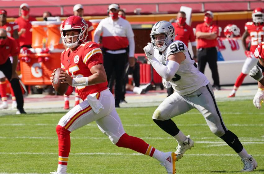 Oct 11, 2020; Kansas City, Missouri, USA; Kansas City Chiefs quarterback Patrick Mahomes (15) runs the ball as Las Vegas Raiders defensive end Maxx Crosby (98) chases during the game at Arrowhead Stadium. Mandatory Credit: Denny Medley-USA TODAY Sports