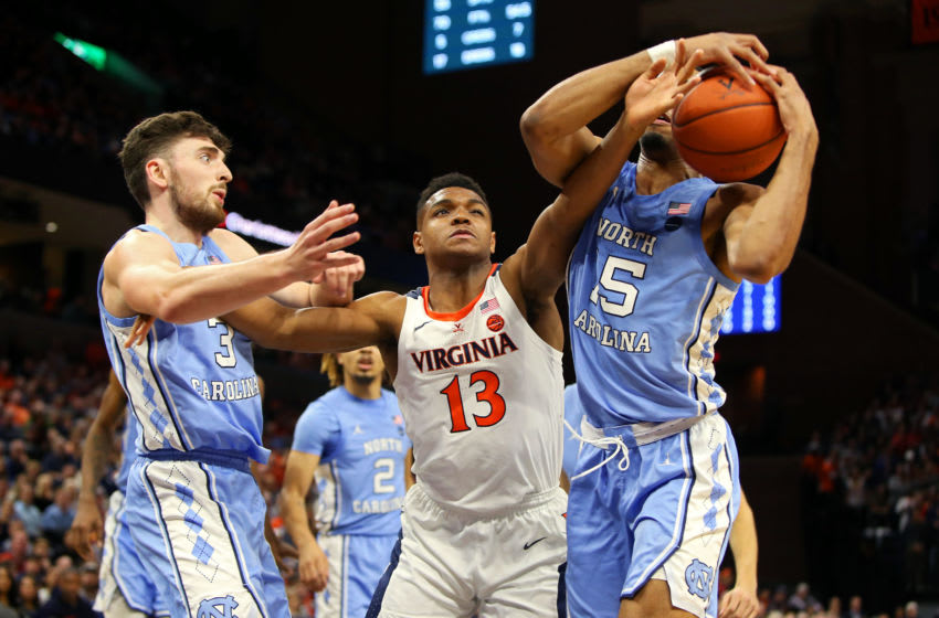 CHARLOTTESVILLE, VA - DECEMBER 07: Casey Morsell #13 of the Virginia Cavaliers fights for a rebound between Andrew Platek #3 and Garrison Brooks #15 of the North Carolina Tar Heels in the second half during a game at John Paul Jones Arena on December 7, 2019 in Charlottesville, Virginia. (Photo by Ryan M. Kelly/Getty Images)