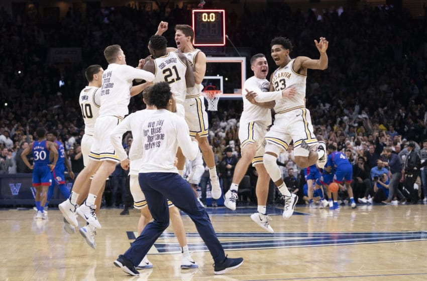 PHILADELPHIA, PA - DECEMBER 21: Cole Swider #10, Dhamir Cosby-Roundtree #21, Collin Gillespie #2, and Jermaine Samuels #23 of the Villanova Wildcats celebrate with their teammates after defeating the Kansas Jayhawks at the Wells Fargo Center on December 21, 2019 in Philadelphia, Pennsylvania. The Villanova Wildcats defeated the Kansas Jayhawks 56-55. (Photo by Mitchell Leff/Getty Images)