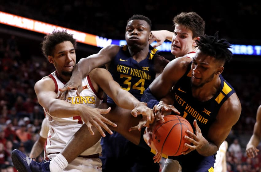 AMES, IA - MARCH 3: George Conditt IV #4 and Michael Jacobson #12 of the Iowa State Cyclones battle with Oscar Tshiebwe #34 and Derek Culver #1 of the West Virginia Mountaineers for a rebound in the second half of the play at Hilton Coliseum on March 3, 2020 in Ames, Iowa. The West Virginia Mountaineers won 77-71 over the Iowa State Cyclones. (Photo by David Purdy/Getty Images)