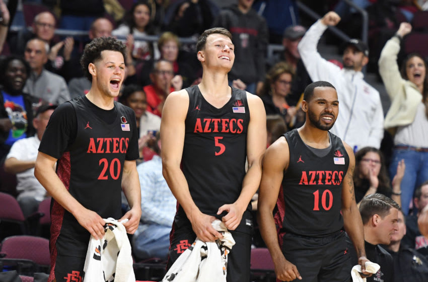 LAS VEGAS, NEVADA - NOVEMBER 28: Jordan Schakel #20, Yanni Wetzell #5 and KJ Feagin #10 of the San Diego State Aztecs celebrate after teammate Joel Mensah (not pictured) #35 dunked against the Creighton Bluejays during the 2019 Continental Tire Las Vegas Invitational basketball tournament at the Orleans Arena on November 28, 2019 in Las Vegas, Nevada. The Aztecs defeated the Bluejays 83-52. (Photo by Ethan Miller/Getty Images)