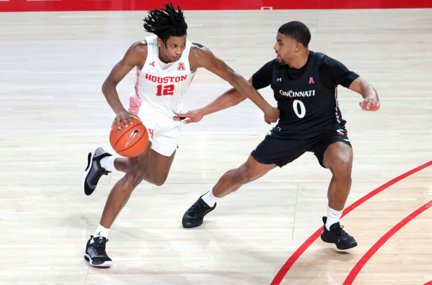 HOUSTON, TEXAS - FEBRUARY 21: Tramon Mark #12 of the Houston Cougars controls the ball against David DeJulius #0 of the Cincinnati Bearcats during the second half of a game at the Fertitta Center on February 21, 2021 in Houston, Texas. (Photo by Carmen Mandato/Getty Images)