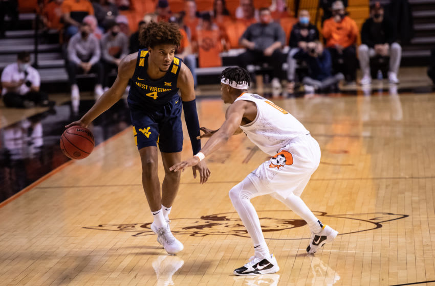 Jan 4, 2021; Stillwater, Oklahoma, USA; West Virginia Mountaineers guard Miles McBride (4) dribbles the ball against Oklahoma State Cowboys guard Avery Anderson III (0) during the first half at Gallagher-Iba Arena. Mandatory Credit: Rob Ferguson-USA TODAY Sports